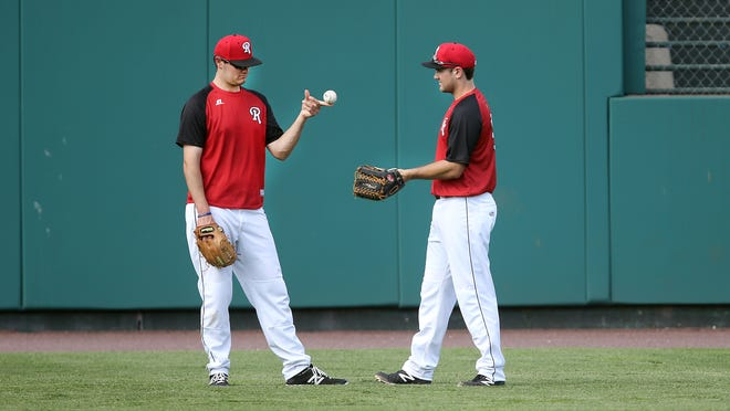 Red Wings pitcher Jason Wheeler, left, shares a light moment shagging balls in the outfield with his brother Ryan Wheeler during batting practice. Ryan just joined the team as a free agent and it's the first time since 1960 that brothers have been teammates on the Red Wings.
