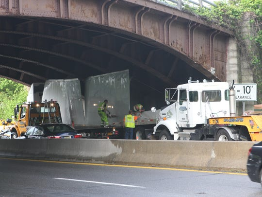 Crews work to remove a tractor-trailer that was wedged under an overpass on the Bronx River Parkway on Wednesday, May 24, 2017.