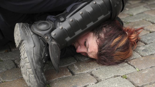In this May 26, 2019, file photo, police detain a woman during a yellow vest protest with other groups in Brussels. The death of George Floyd has renewed scrutiny of immobilization techniques long used in policing around the world.