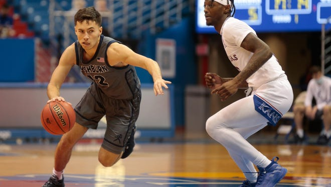 Washburn senior Tyler Geiman manuevuers past Kansas senior Marcus Garrett in the first half of Thursday's game at Allen Fieldhouse in Lawrence. Geiman had nine points and seven assists but the Ichabods lost 89-54.