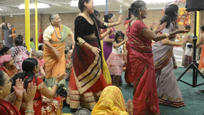 A group of women dances to music as others seated clap and sing along during a Puran celebration in Burlington on Sunday.