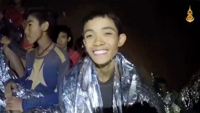In this July 3, 2018, image taken from video provided by the Royal Thai Navy Facebook Page, a Thai boy smiles as Thai Navy SEAL medic help injured children inside a cave in Mae Sai, northern Thailand. The Thai soccer teammates have been stranded more than a week in the partly flooded cave. They said they were healthy on a video released Wednesday, as heavy rains forecast for later this week could complicate plans to safely extract them.