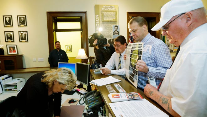 Initiative promoter Tim Eyman, second from right, files a new anti-tax initiative Wednesday, Nov. 18, 2015, with Kay Ramsay, left, a programs specialist with the secretary of state's office in Olympia, Wash. If passed, the initiative would put a one-year limit on tax increases in Washington state unless approved by a two-thirds vote of the Legislature or a majority vote of the people. (AP Photo/Ted S. Warren)