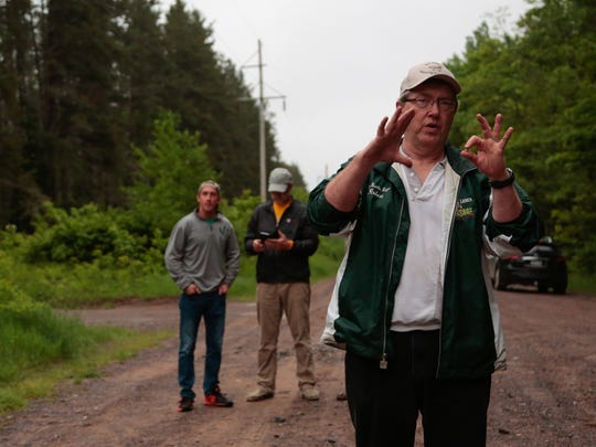 Bob Anderson, of L'Anse, talks about the story behind the Paulding Light while bringing his family and friends to witness the mysterious light appear off of Robbins Pond Road in Paulding, Mich., on Wednesday June 13, 2016 in Michigan's Upper Peninsula.