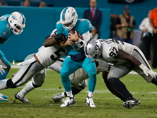 FILE - In this Sunday, Nov. 5, 2017, file photo, Miami Dolphins quarterback Jay Cutler (6) is sacked by Oakland Raiders outside linebacker Bruce Irvin (51), middle linebacker NaVorro Bowman (53) and defensive end Mario Edwards (97) during the second half of an NFL football game in Miami Gardens, Fla. The Dolphins (4-4) are alive in the AFC despite back-to-back losses to Baltimore and Oakland. They face the Carolina Panthers on Monday night. (AP Photo/Wilfredo Lee)
