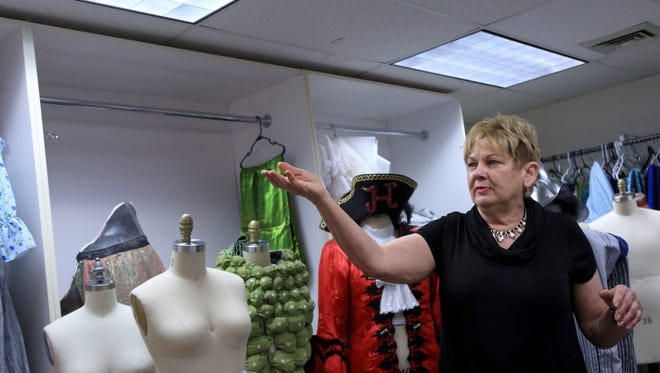 """Wilma Mickler, manager of Tuacahn's costume shop, shows off some of the costumes for the Ivins City amphitheater's production of """"Peter Pan"""" this summer."""