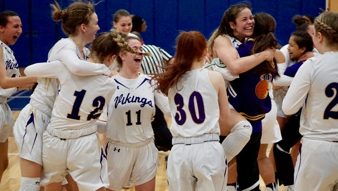 North Kitsap girls basketball players celebrate Saturday's regional win against Renton. The VIkings are headed to the state tournament for the first time since 1988.
