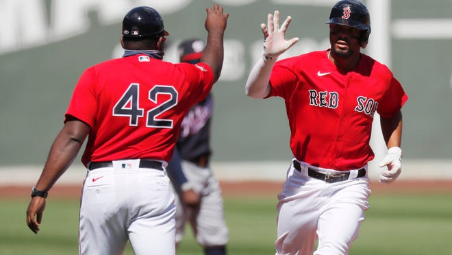 Boston's Xander Bogaerts, right, is greeted by third base coach Carlos Febles after hitting a two-run homer in the first inning.