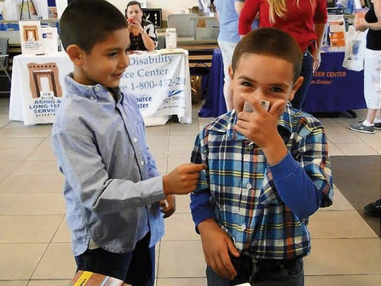 Leonel and Christopher Meraz, ages 7 and 6, get a whiff of a scratch and sniff card — so they know what natural gas smells like — at the annual Neighborhood Expo at City Hall the first Saturday in May.