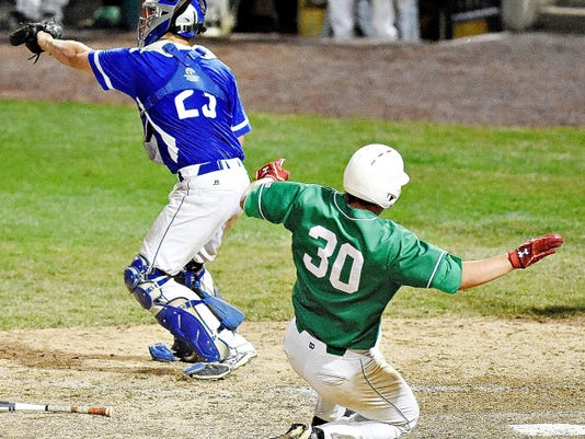 Spring Grove's Derek Hoiles, left, catches the ball as Donegal's Christopher Beaudoin, right, slides into home during the District 3-AAA championship game at Santander Stadium in York on Thursday. Spring Grove would fall to Donegal, 11-5.