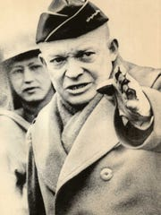 Preparing for the invasion of Europe, General Eisenhower gestures during a review of tank maneuvers in Britain early in 1944. On June 6, he directed the landings on Normandy's beaches. AP photo