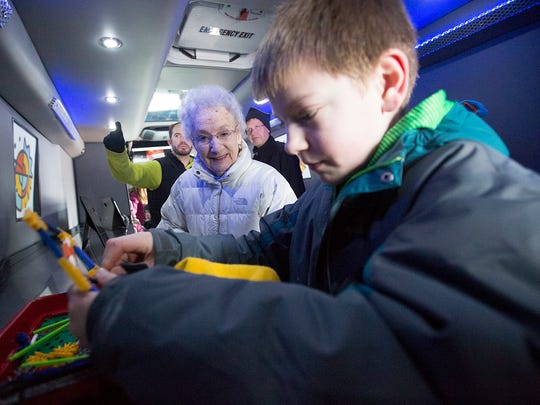 Ruth Schultz of Wausau, left, watches as Porter Rammer, 11, of Marshfield play with K'NEX inside the Vortex Mobile Lab, which is part of the STEM Scouts program during the fifth annual Winter Fest in downtown Wausau.