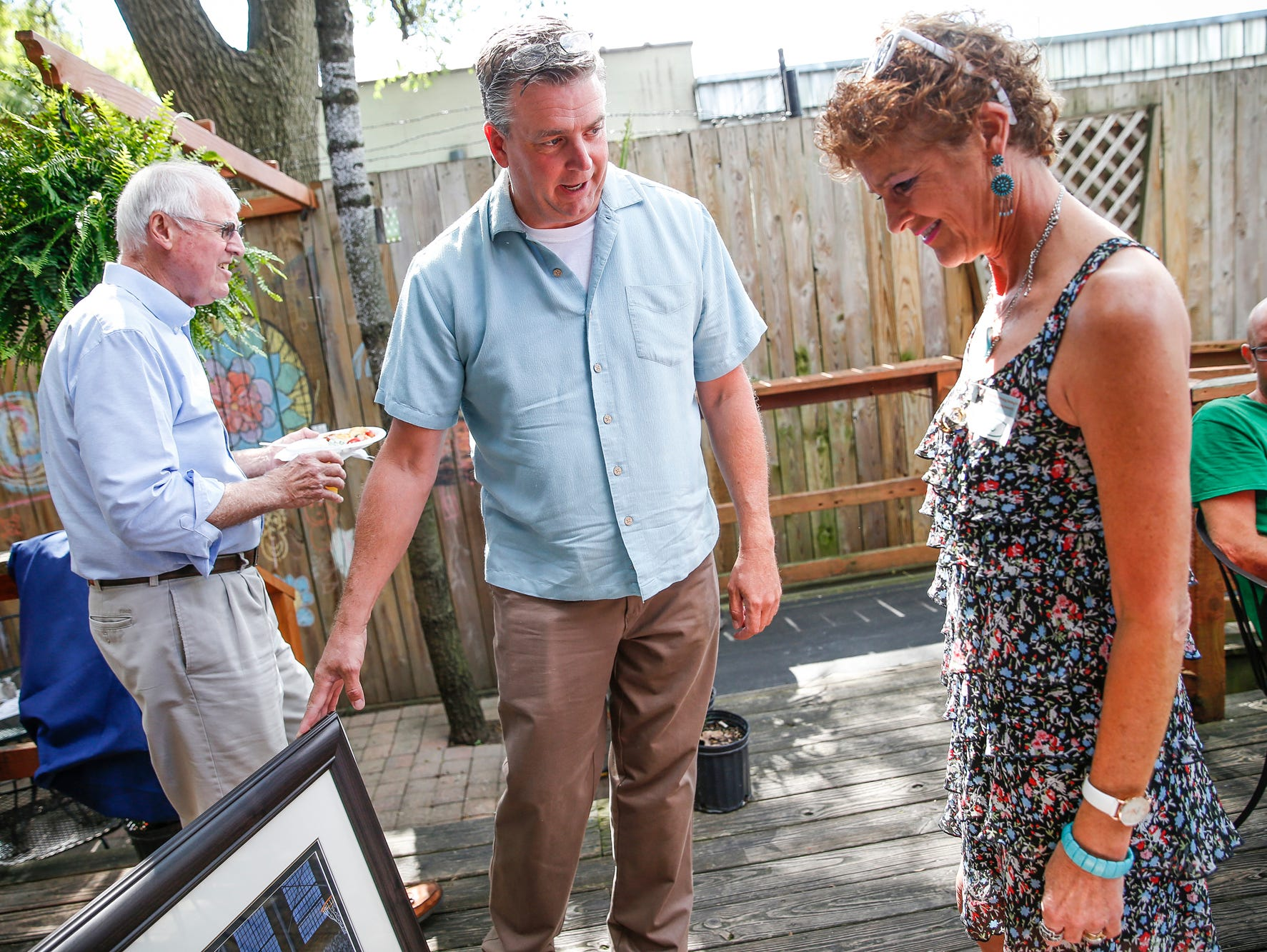Artist Anthony Padgett shows Kelli Piechocki, daughter of Bobby Plump, a commissioned painting of Plump's game winning shot against Muncie Central during Plump's 80th birthday party on Sept. 11, 2016.