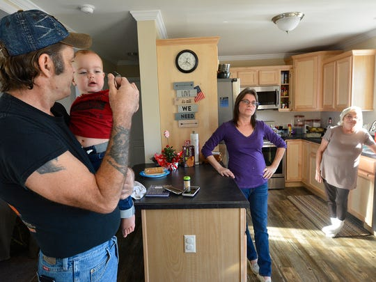 George Whitmoyer holds his grandson Asher, while his wife Nachelle and her family prepare Thanksgiving dinner in their new home, Thursday, Nov. 23, 2017. The family lost their Kralltown home on Thanksgiving eve last year to fire. John A. Pavoncello photo
