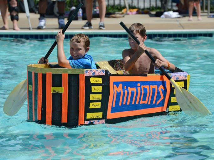Peyton Naugle, 11, front and Owen Murray, 9, paddle their cardboard boat they made at the Delmar Kids Club during the race Friday. A fleet of boats representing the Fruitland, Delmar, North Salisbury, Westside Intermediate and the Westside Community CenterÊcamp locations came together to show-off their creations and compete for bragging rights.Ê Each camp location created a cardboard craft for the competition and decorated it to reflect the weekly theme of their camp.Ê Each boat will be powered by paddles and kid powerÑmaking for a great race to the finish line.
