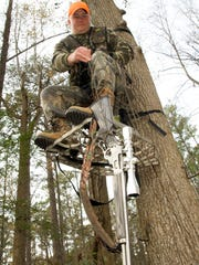 A hunter uses a rope to raise his rifle up to his tree stand. Tree stand falls are the No. 1 cause of hunting-related deaths.