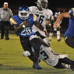 Nathan Anpadu, No. 25 of the Washington Wildcats, drags a E. Gadsden Jaguar defender with him as he picks up some extra yardage in the second quarter of their kickoff classic varsity half-game Friday night at Washington High.