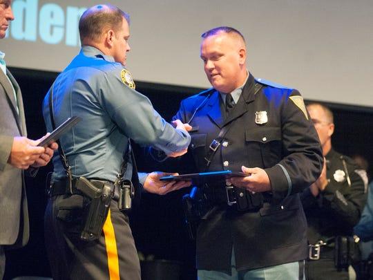 Vineland K-9 Officer Dwight Adams, right, receives