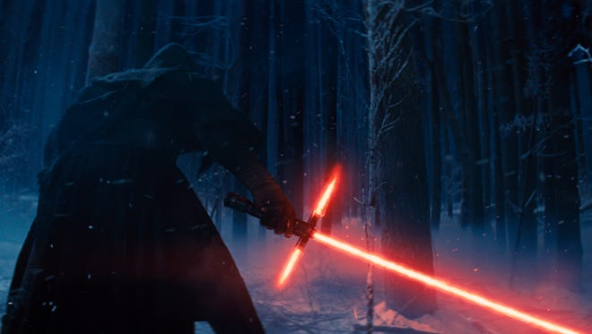 """This photo provided by Disney shows Adam Driver as Kylo Ren, with his Lightsaber, in a scene from the new film, """"Star Wars: The Force Awakens."""" The movie releases in the U.S. on Dec. 18, 2015."""