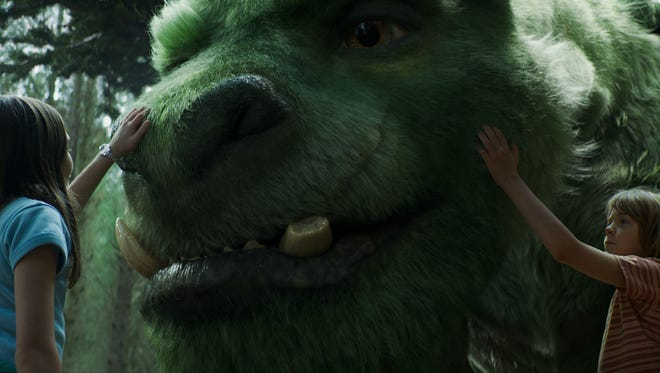 """Oona Laurence as Natalie, left, and Oakes Fegley as Pete, right, with Elliot the dragon, in a scene from """"Pete's Dragon."""""""