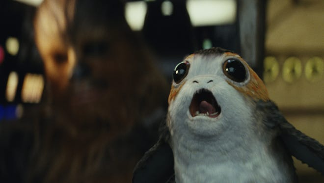 """This image released by Lucasfilm shows Chewbacca, left in background, and a Porg in a scene from """"Star Wars: The Last Jedi."""