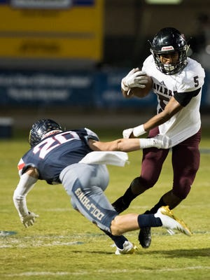 Navarre High School's Dante Wright, (No. 5) gives Gulf Breeze High School's Nate Herrick, (No. 20) the slip during the Dolphins final regular season home game Friday night.