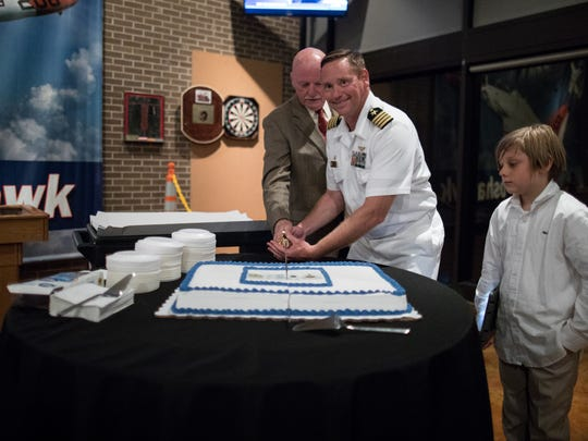 Captain Erik Spitzer and Dave Carey use a saber to cut a cake during Naval Air Station Kingsville's 75th anniversary celebration on Friday, June 30, 2017.