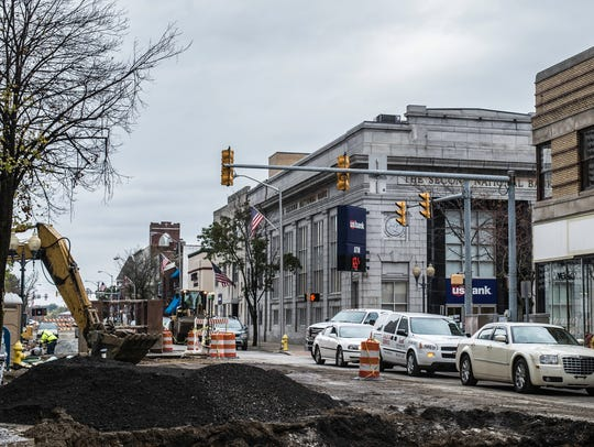 Cars drive past orange constuction on southbound Eighth