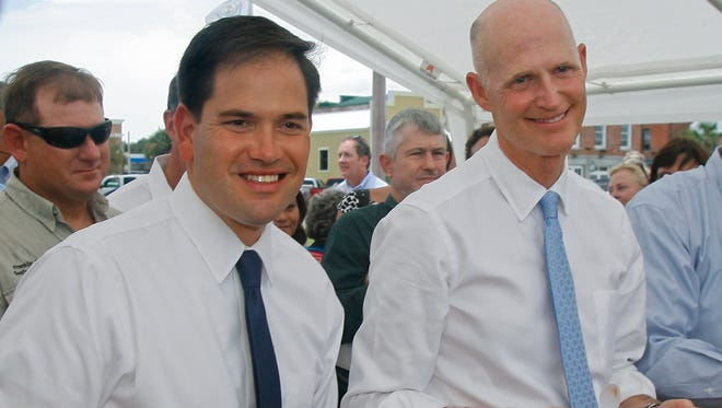 U.S. Sen. Marco Rubio and Florida Gov. Rick Scott smile for the cameras before eating their oysters Tuesday, Aug. 13, 2013, in Apalachicola, Fla.