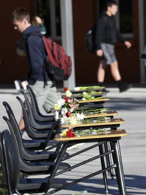 At Viera High School, students walk past 17 empty chairs in their courtyard during the National School Walkout - one seat for each of the people who died in a shooting at Marjory Stoneman Douglas High.