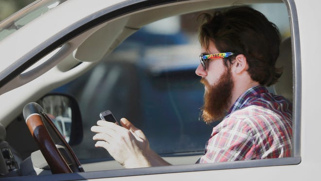 In this Feb. 26, 2013, file photo, a man uses his cellphone as he drives through traffic in Dallas. A growing number of states and cities are raising penalties and broadening texting while driving bans.