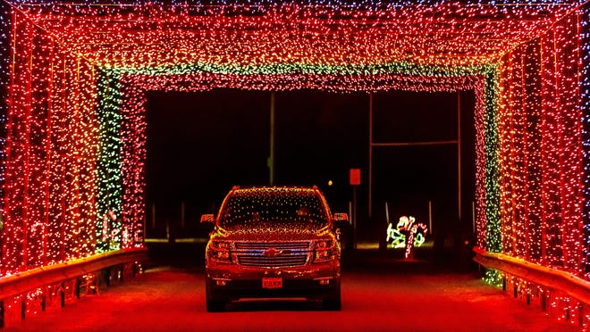 With their lights turned off to take in the lights, a pickup-truck is illuminated for a short moment as the synchronized lights turn on in unison as it makes it's way through the lighted tunnel during the Chatham Friends of the Parks' drive-through holiday light display in 2017.