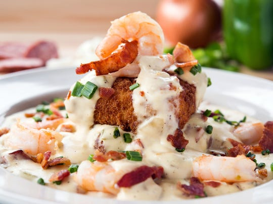 Shrimp and grits at Metro Diner features two fried grit cakes infused with cheese, roasted red peppers and Andouille sausage topped with shrimp, sausage, onions and peppers in a shrimp sauce garnished with chopped bacon and green onions.