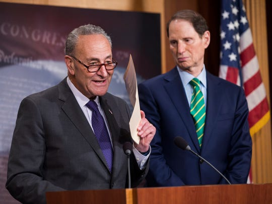 Senate Minority Leader Chuck Schumer, alongside Sen. Ron Wyden, speaks to the media about the Republicans' tax framework in the US Capitol on Sept. 27, 2017.