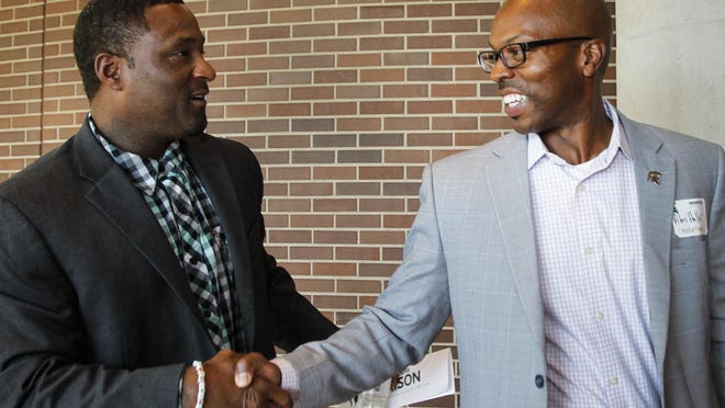 Senior Associate AD Alan Haller greets former MSU standout and former teammate Andre Rison, left.