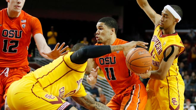 Oregon State's Malcolm Duvivier attempts to get through the defense of Southern California's Darion Clark, second from left, and Jordan McLaughlin, right, alongside teammate Drew Eubanks during the first half of an NCAA college basketball game, Wednesday, March 2, 2016, in Los Angeles.