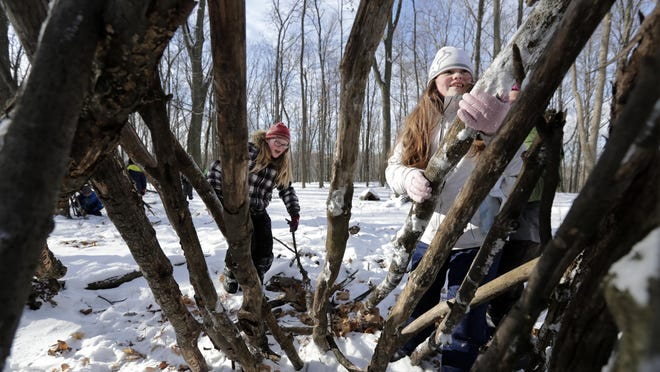 Lily Tomas, left, and Willow Stulo, fifth-graders at Butte des Morts Elementary School in Menasha, gather and place branches to make a survival shelter during a field trip Feb. 9 to 1000 Islands Environmental Center in Kaukauna.