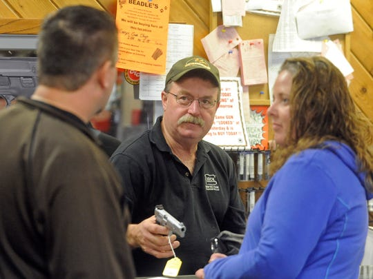 Steve Naatjes, owner of Gary's Gun Shop in Sioux Falls, shows merchandise to customers in this 2012 file photo.