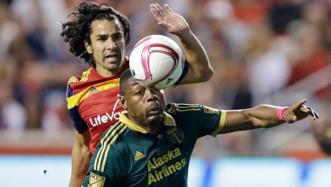 Portland Timbers forward Fanendo Adi (9) and Real Salt Lake defender Tony Beltran, rear, battle for a loose ball in the first half during an MLS soccer game Wednesday, Oct. 14, 2015, in Sandy, Utah.