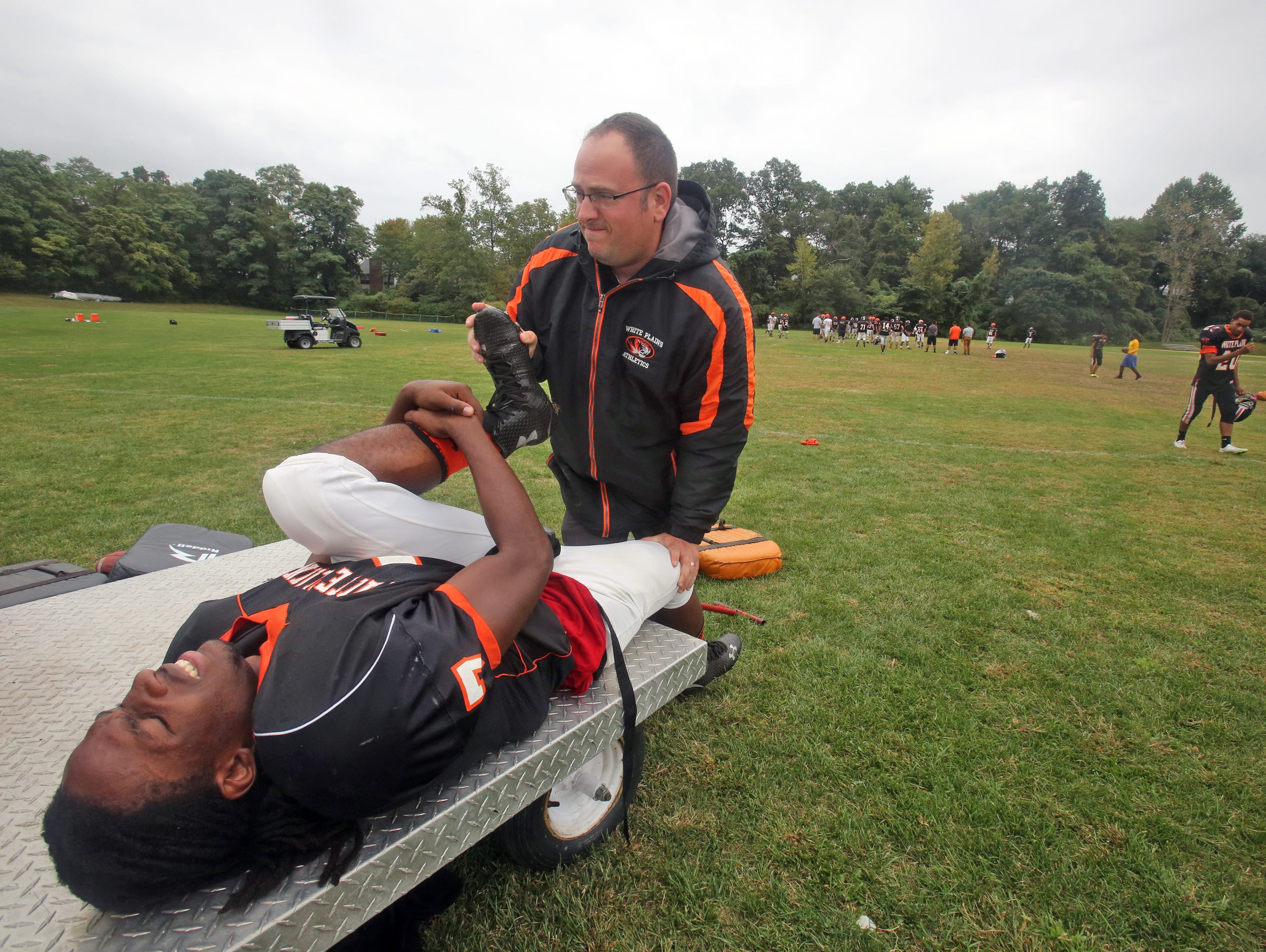White Plains High School football player Eddie Thomas has his leg stretched by athletic trainer Mike Mirabella during practice Sept. 29, 2015.