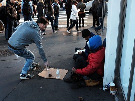 Homeless men panhandle on the streets of New York City
