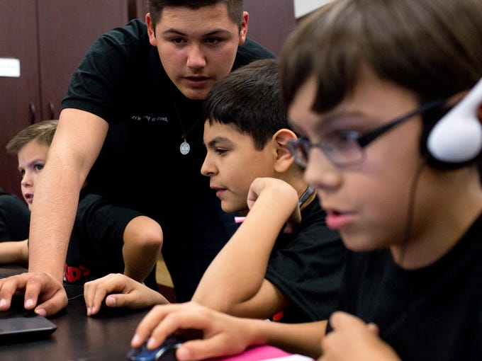Victor Bueno works with students during an iCode Kids