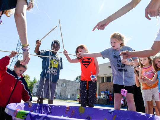 Kids fish for prizes as they play free carnival games at the Holly House Fun Fair Sunday, September 10, 2017.