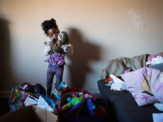 Tyanna Hunter, 5, grabs one of her favorite toys out of a box before her family leaves their room at the Economy Inn on Thursday, January 25, 2018.