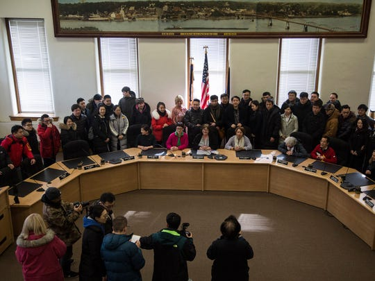 Zhejiang Symphony Orchestra, visiting from China, gather for a group photo on Wednesday, Feb. 21, 2018, in the Muscatine city council chamber.