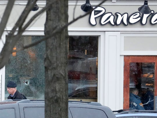 A hole is seen on a glass panel as a man leaves a Panera