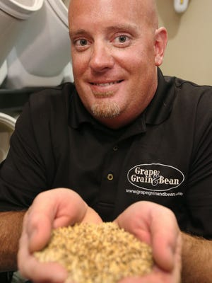 Marcus Mecca poses for a photo with a handfull of malt at Grape, Grain and Bean on Thursday, June 16. The store carries over 30 types of malts.