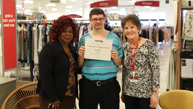 Mason Martin holds his three-year employment recognition from TJ Maxx (middle) with manager Mary and coworker Nancy.