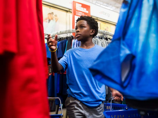 Boys & Girls Clubs of the Tennessee Valley kid Antwain Burdine Jr., 10, picks out shorts at Academy Sports & Outdoors in West Knoxville Wednesday, July 26, 2017. 30 boys & girls from the club got to each go on a $100 shopping spree for back to school items at the store.
