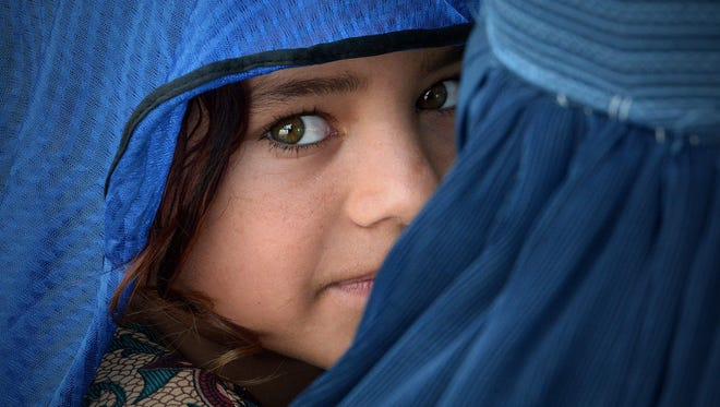 An Afghan woman carries her girl during the visit of the United Nations High Commissioner for Refugees, Filippo Grandi (unseen) at the Azakhel Voluntary Repatriation Centre in Nowshera. The United Nations High Commissioner for Refugees Filippo Grandi is on an official three-day visit to Islamabad.